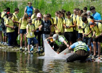 Students observe fish and organisms caught in a seine net along the Onondaga Lake shoreline.
