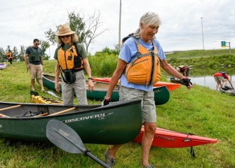 "Ami Kadar (foreground), of Syracuse, a first-time Corps participant, prepares to launch her canoe.  Ami later said the experience was ""wonderful, really beautiful"" and that she took a lot of photos during the paddle."