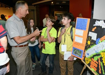Students Symeon Barrett (center) and Peter Santoro (right) discuss their poster about channelizing Onondaga Creek and how it changed the creek ecosystem.