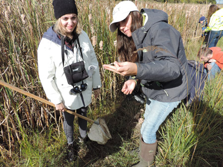 "Onondaga Community College student Kaitlyn Jordan (left), and Alivia Sheffield, YNLT volunteer and Piping Plover Project Coordinator with the New York State Office of Parks and Recreation and Historic Preservation, examine a shed snakeskin found in a wetland area on the western shoreline.  ""Understanding and knowing the past of this area, it was incredible the amount of biodiversity we were able to find, from small macroinvertebrates to bald eagles and coyote prints,"" said Sheffield. ""This ecosystem is starting to thrive once again. Saturday not only showed that, but that the community cares and is willing to put in the effort to keep it that way."""