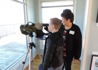 Michele Neligan, a former Onondaga Audubon board member and a photographer exhibiting at the event, helps 10-year-old Ethan Jackson, of Elbridge, New York, use a scope to identify a red-breasted merganser.