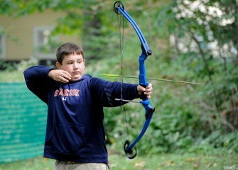 Eleven-year-old Evan Perkins, of Syracuse, releases an arrow after aiming at a target in the archery area.