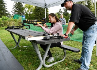 Sixteen-year-old Elise Dougherty, of Liverpool, learns how to use a crossbow from Onondaga County Parks Commissioner Bill Lansley.