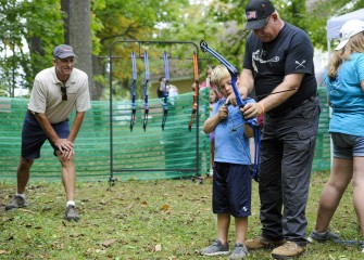 Honeywell Syracuse Remediation Program Manager Steve Miller (left) watches as Robert Murray, of Elbridge, learns how to properly line up, or nock, an arrow on the bow string in the archery area.
