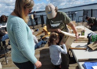 Forty-three volunteers gathered at the Onondaga Lake Visitors Center and along the shoreline to build and install nesting boxes on Saturday, September 29. Eleanor Sunkes, 3, decorates a bird box held by Barbara Kamerance of Central Square as Eleanor's mom looks on.
