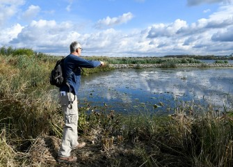 A seed bag tossed by Joe Hansen, of Liverpool, splashes into wetlands along the southwest shoreline.