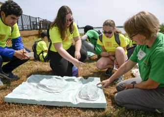 Students (left to right) Ahmad Hassan, Cadence Massulik and Riley Abbott from Team Yellow work with a watershed model with lead science counselor Gretchen Messer, visiting professor at SUNY ESF.