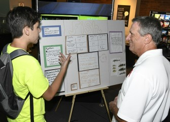 Kevin Fratostitanu, from Manlius Pebble Hill School, discusses findings about fish with Honeywell Syracuse Program Manager Stephen Miller on Discovery Day at the MOST.
