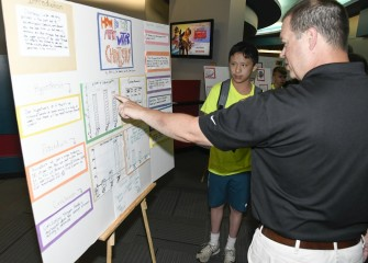 Aiden Lee, from Wellwood Middle School, shows a visiting parent his group's findings on water chemistry.